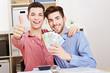 Schwules Paar mit Geldscheinen hält Daumen hoch