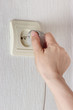 Hand inserting electric plug in the socket on the wall