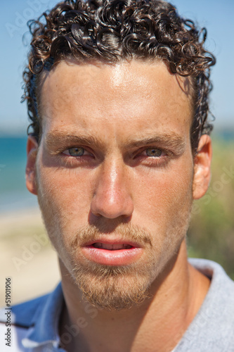 Portrait of a handsome young mediterranean man with curly hair