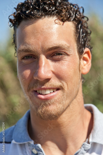 Teenager with curly hair in front of a corn field