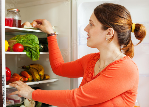 Young housewife near refrigerato