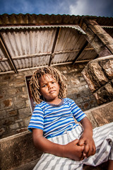 Rasta little boy sulking on the porch