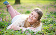 Portrait of a young woman lying on grass outdoors