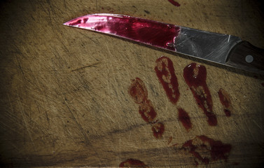 wooden background with a bloody hand print on the cutting board