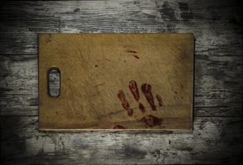 Grunge wooden background with a print of a bloody hand