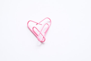 Office romance. Pink paperclips forming a heart.