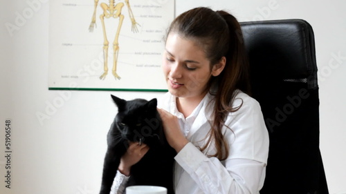 Young female vet with black cat