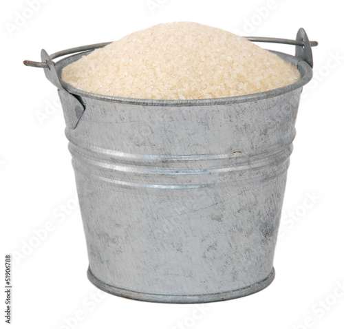 Golden granulated sugar in a miniature metal bucket