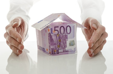 Male hands giving energy to money house
