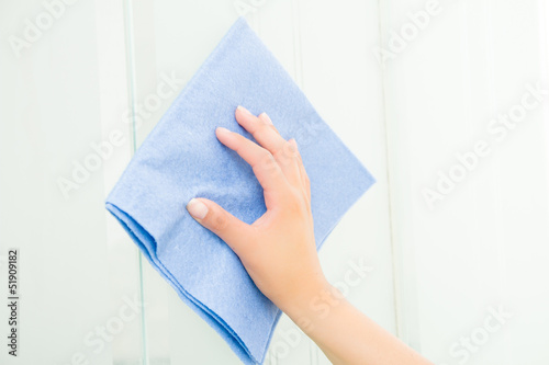 Hand with blue sponge cleaning the bathroom glass - 51909182
