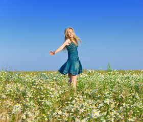 The beautiful happy young woman in the field of chamomiles