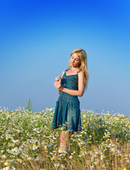 happy young woman in the field of chamomiles