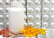 liquid capsules and silvery plates of medicines near a bottle..