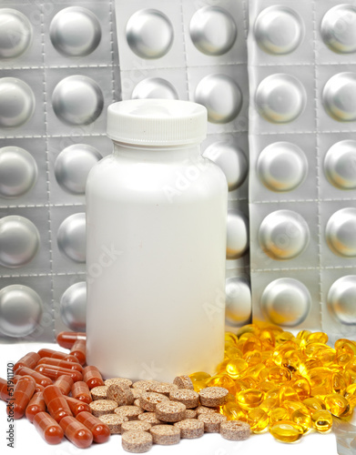 Yellow liquid capsules and silvery plates of medicines