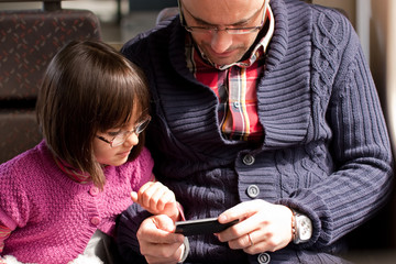 Father and daughter on train with smart phone
