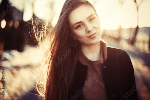Fashion outdoor portrait of young attractive brunette