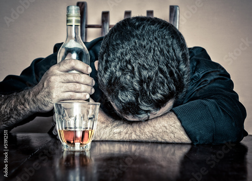 Grunge portrait of a drunk man sleeping with his head on a table