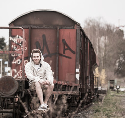 Sebastian sits on the railroad car