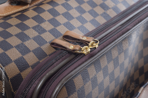 Photo of zip on a checkered bag. close up.