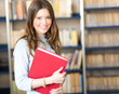 Young student holding a book in a library