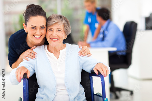 adult daughter accompanying senior mother visiting doctor
