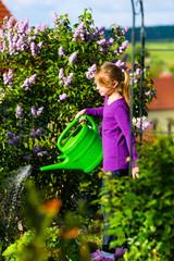 Happy child watering flowers in the garden