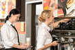Two waitresses serving coffee with machine