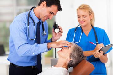 ophthalmologist examining senior woman's eye