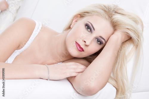 Hübsche blonde Frau liegt auf  der Couch
