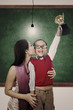 School champion holding trophy kiss by mum in class