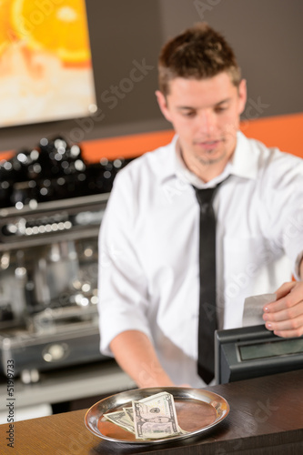 Young bartender in uniform taking cash dollar