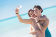 Young Couple Taking Self Portrait with Mobile at Beach