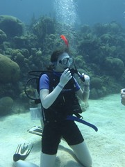 Female Scuba Diver Kneeling on the Ocean Floor