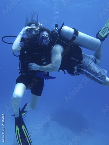 Couple posing underwater while scuba diving on vacation