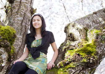 Young teen girl sitting on branches of flowering cherry tree