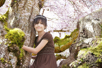 Young biracial girl sitting in  flowering cherry tree