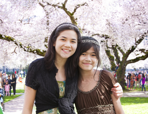Two girls standing in front of large flowering cherry tree