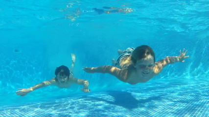 Two Boys Jumping Into Pool Then Swims Underwater To Camera