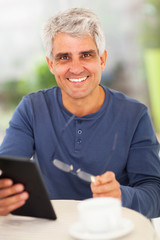 happy middle aged man with tablet computer