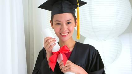 Mixed Race Asian graduate with diploma