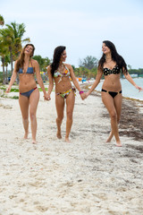 Three laughing women in bikinis