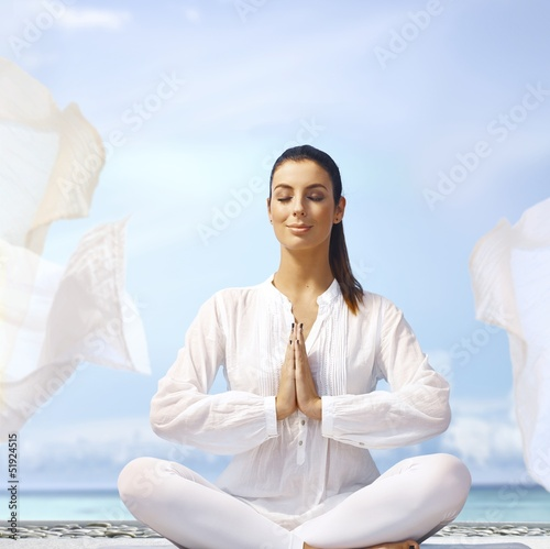 Young woman meditating on the coast