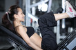 Woman at the gym doing exercises to strengthen muscles of legs