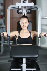The girl is engaged in the gym doing exercise strengthens chest