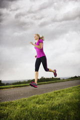 Female Runner working out dramatic clouds