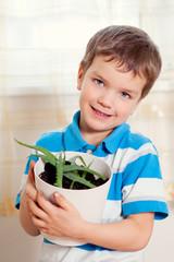 boy puts plant in pot