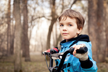 Portrait of serious boy with bicycle in park