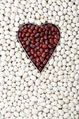 Red beans in heart shape among white beans