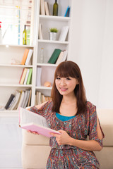 chinese girl reading on sofa lifestyle photo