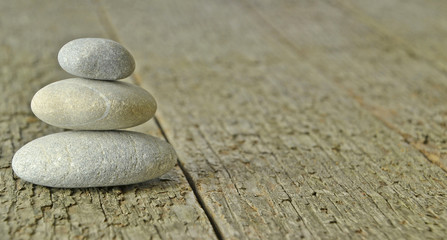 A small pile of stones on a wooden background with copy space